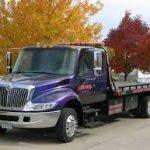 Purple flatbed tow truck service